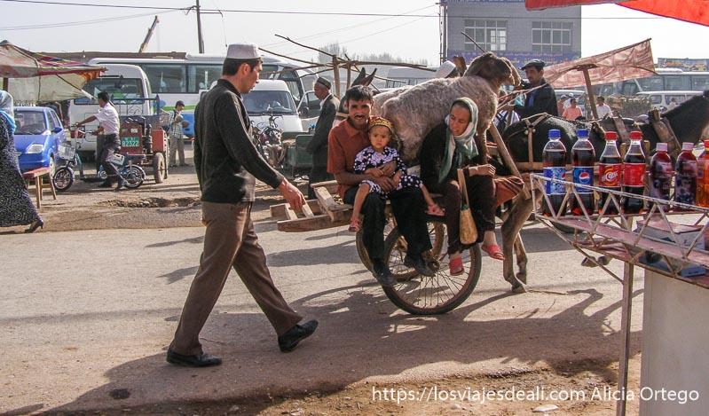 padres y niño sentados en un carro junto a dos ovejas mercado de Kashgar