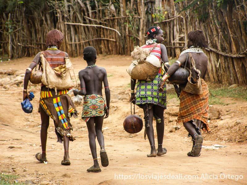 tres mujeres y una niña andando por el mercado cargadas con calabazas mercados del sur etíope