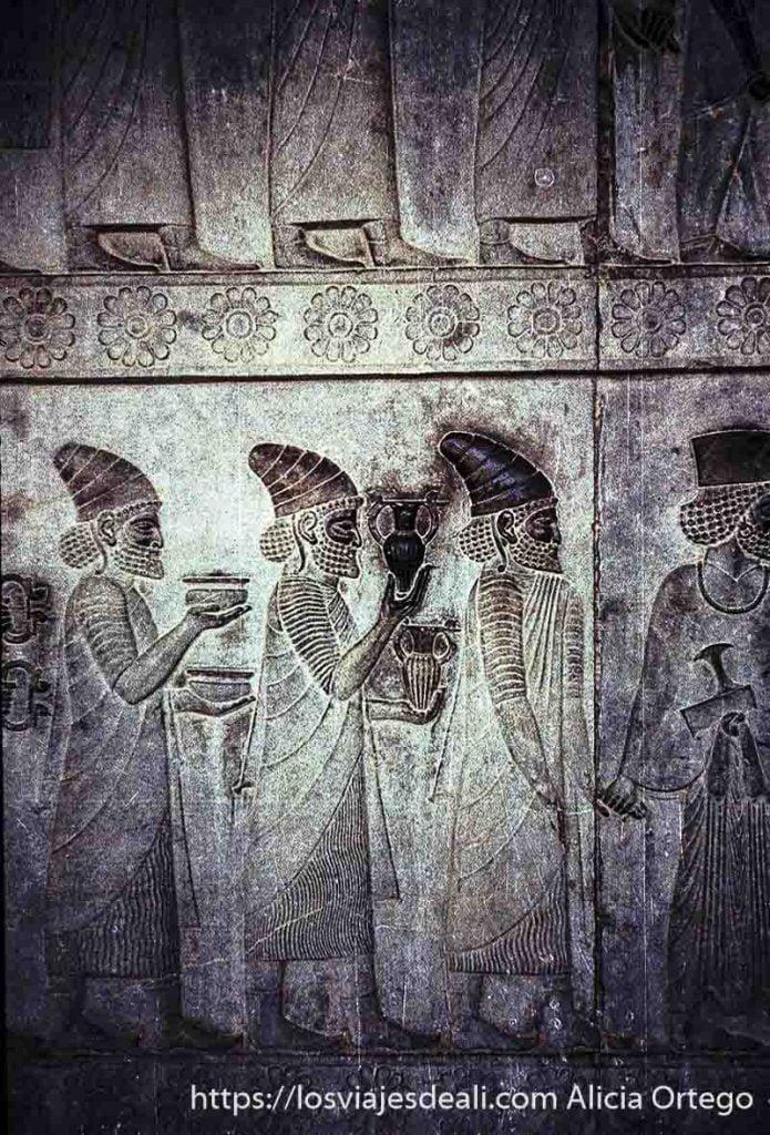 bajorrelieves de fenicios con sus barbas rizadas y gorros llevando regalos en persépolis