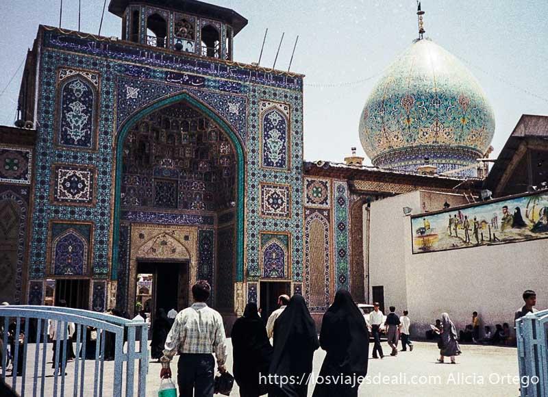 entrada al mausoleo de shiraz con puerta y cúpulas llenas de de azulejos