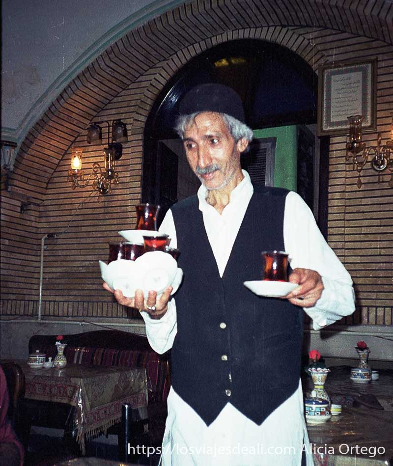 camarero con 12 vasos de té con sus platillos en una mano en teherán