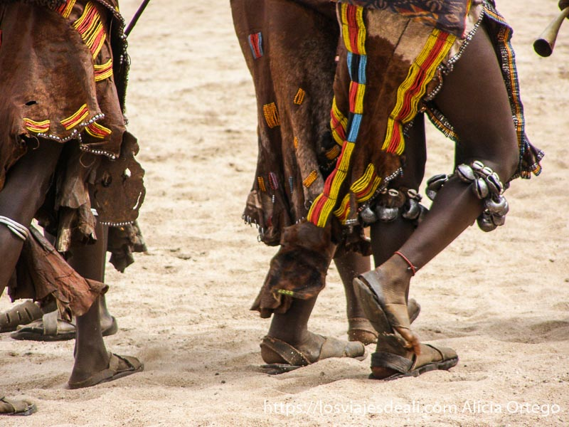 pies de mujer con cascabeles debajo de las rodillas andando por la arena tribu hamer