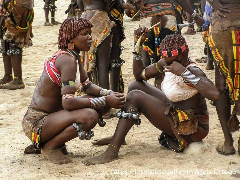 dos mujeres hamer sentadas en la arena con sus heridas en la espalda tribu hamer