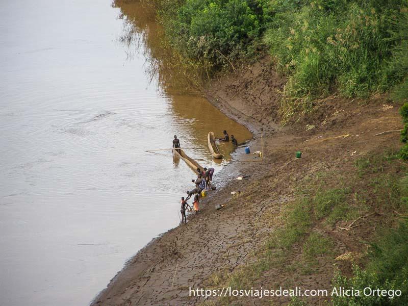 hombres y mujeres de la tribu karo lavándose en la orilla del río omo
