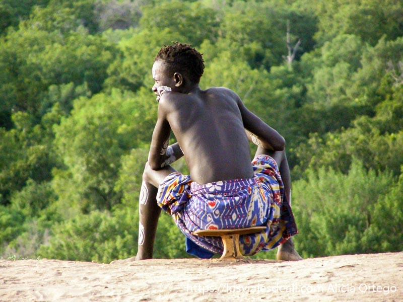 chico de la tribu karo sentado en su banqueta mirando al río