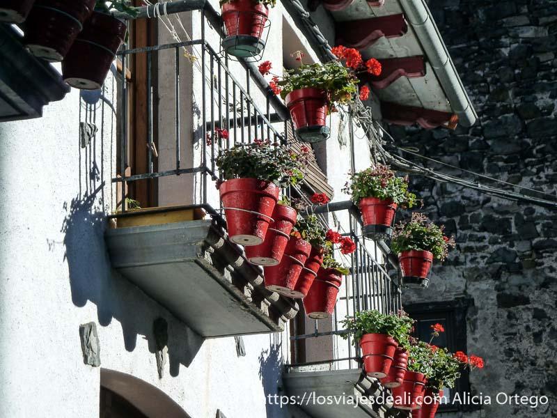 balcones con tiestos rojos y geranios del mismo color en isaba valle del roncal