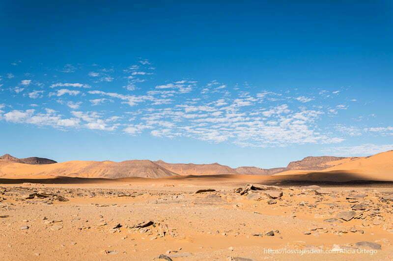paisaje de dunas, rocas y cielo con nubecillas