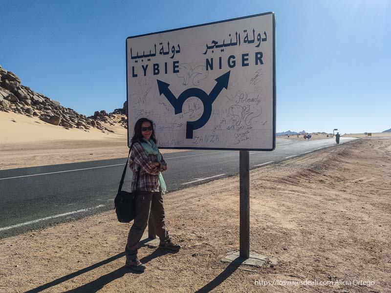 posando junto a cartel de carretera que señala dirección a Níger y Libia viaje a Argelia