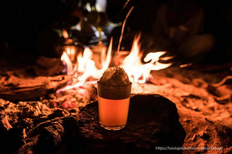 vaso de té con gorro de espuma y el fuego detrás