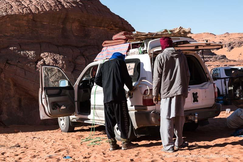 tuaregs echando gasolina al coche de una garrafa con una goma en el desierto