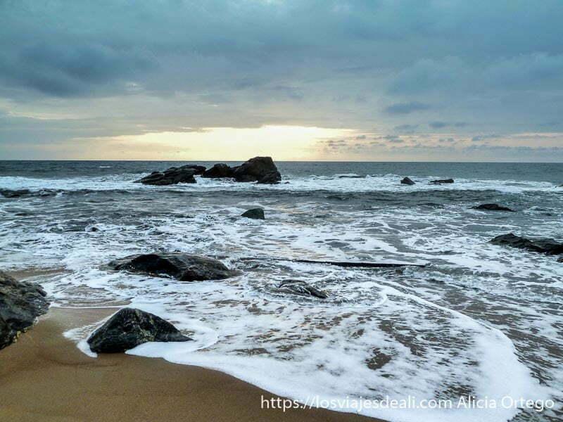puesta de sol con espuma de olas y rocas en camerún