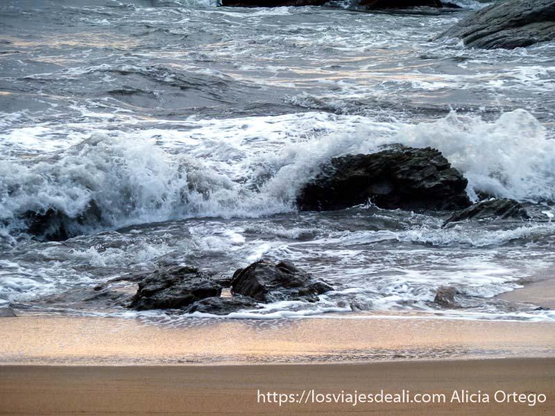 olas rompiendo en rocas de la orilla con luz naranja de atardecer costa del sur de camerún