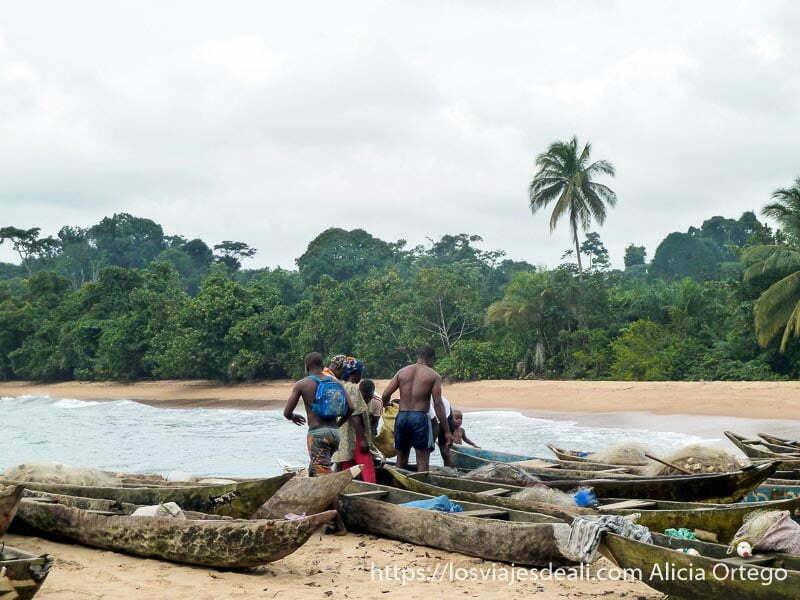pescadores entre barcas en la playa camerún