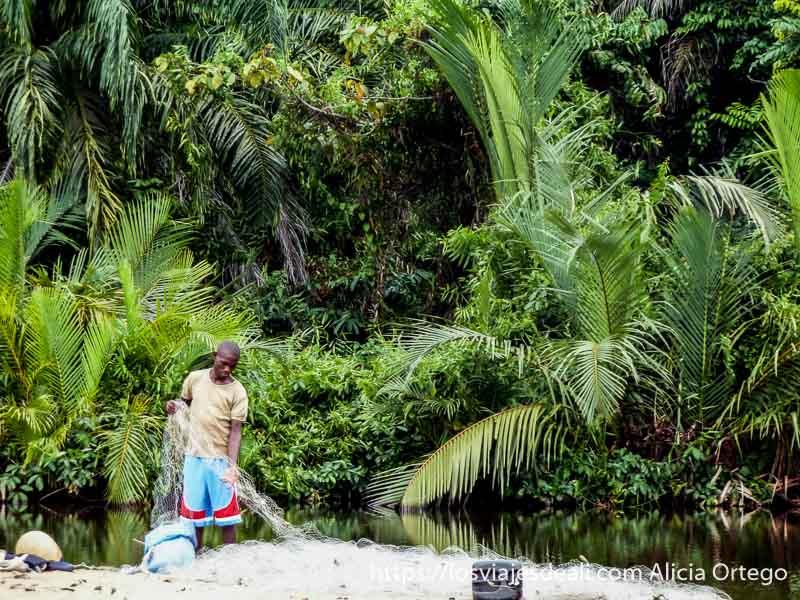pescador con su red junto a lago de agua dulce en camerún