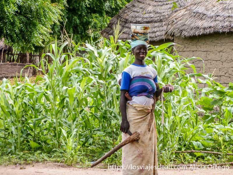 mujer sonriente con palangana en la cabeza, hacha neolítica en la mano y bebé a la espalda carreteras de camerún