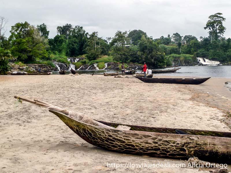 barcas en la arena y al fondo las cascadas de la lobe