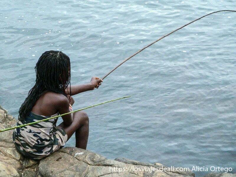 niña pescando con un junco largo en cascadas de la lobe