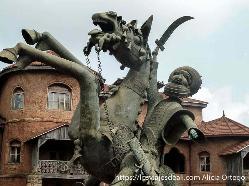 estatua del sultán de foumban montado a caballo con espada en alto