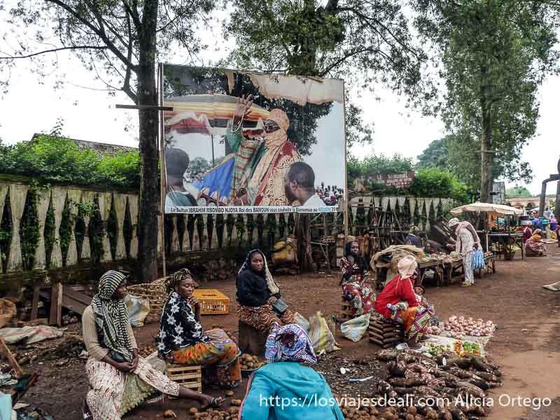 mujeres vendiendo sus mercancías bajo cartel del sultán de foumban