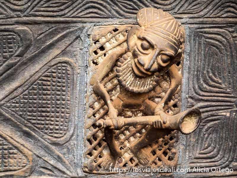 figura de bronce de música con trompeta en la mano en puerta de foumban