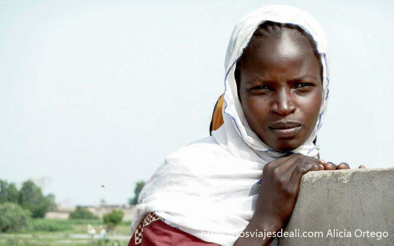 chica de camerún con velo blanco en la cabeza mirando al infinito hacia los montes mandara