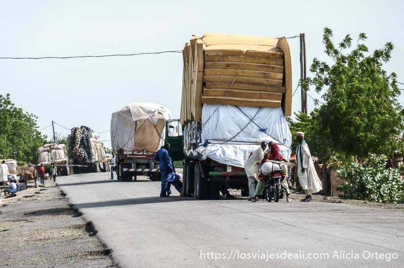 camiones en la carretera cargados hasta doblar su altura hacia los montes mandara