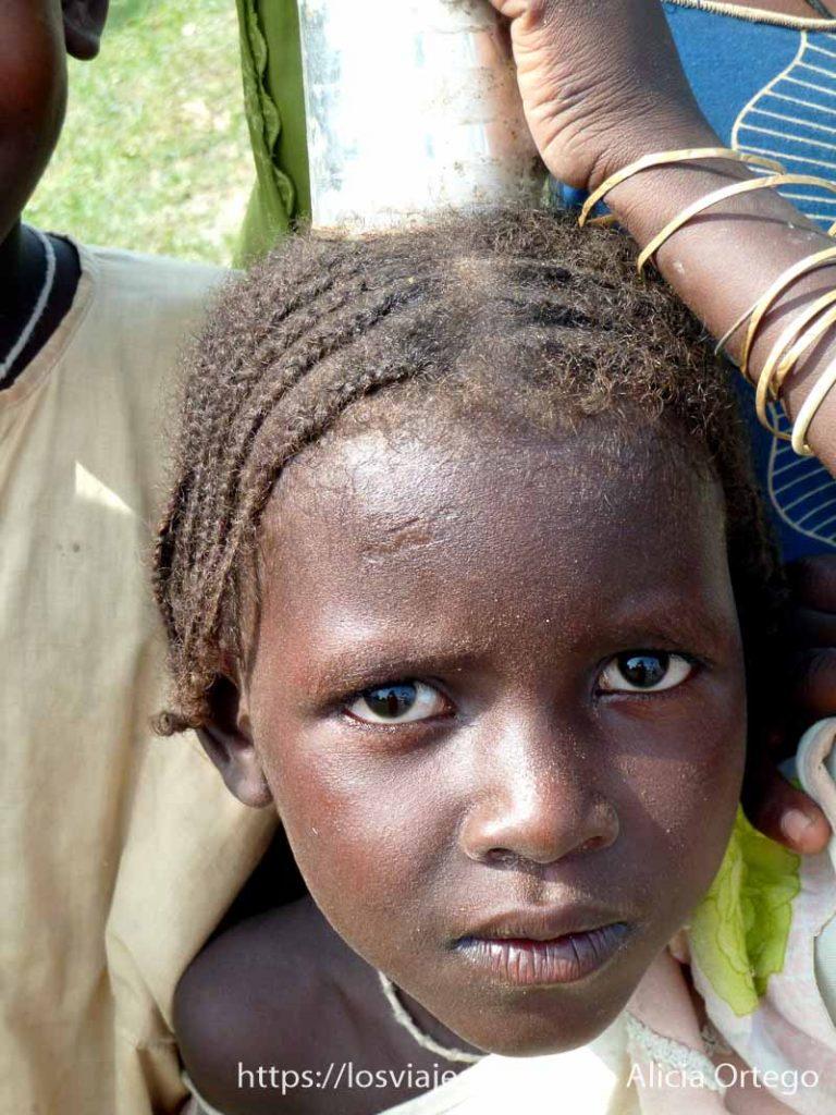 niña con trencitas mirando fijamente a la cámara hacia los montes mandara