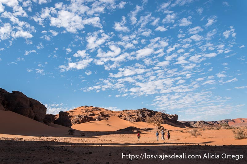 viajeros en el desierto con cielo enladrillado de nubes blancas paisajes del sahara