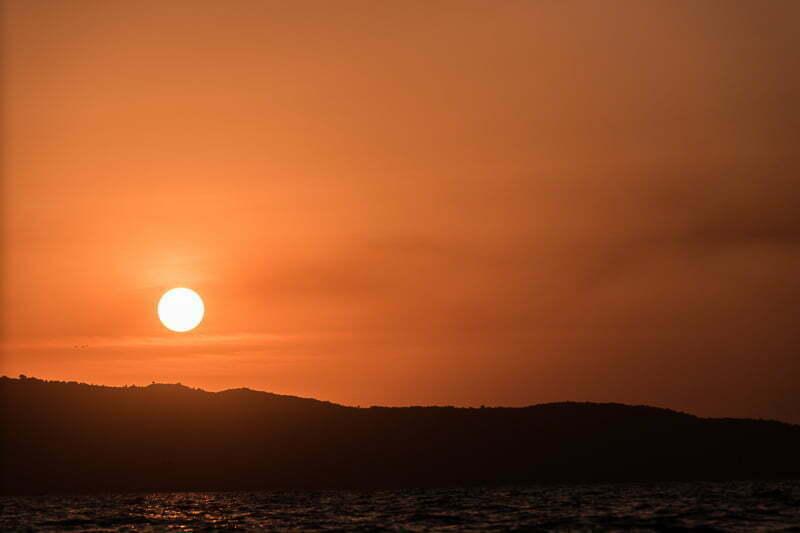 atardecer de cielo naranja con el sol a punto de ocultarse en el lago victoria