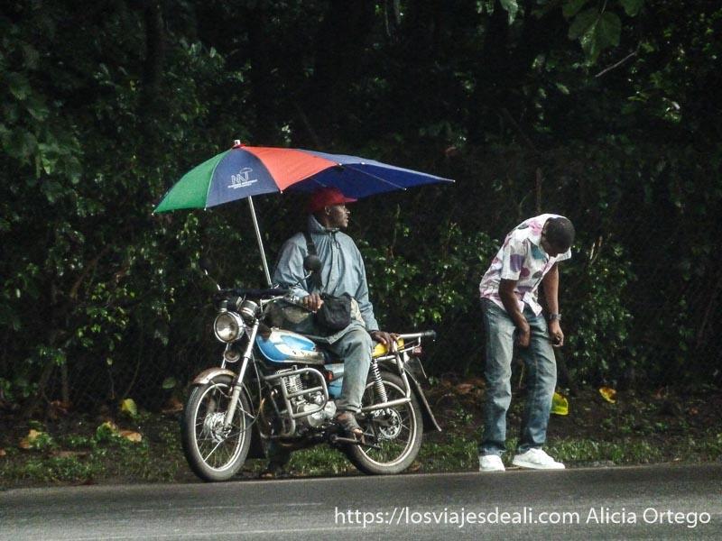 moto con paraguas con extensión para asiento de atrás y cliente recién bajado en limbe