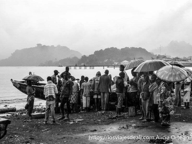 gente rodeando barca de pescado mientras llueve en limbe