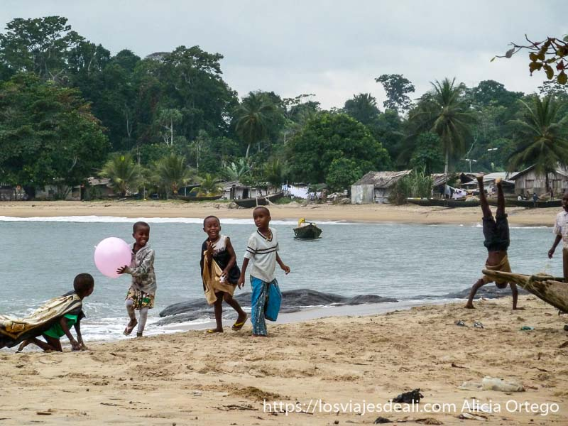 niños de londji en la playa jugando con globo rosa