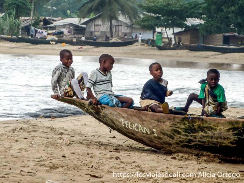 niños de londji sentados en una barca en la playa