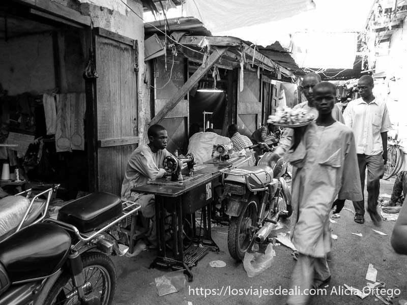 chico llevando plato de buñuelos entre los sastres en el mercado