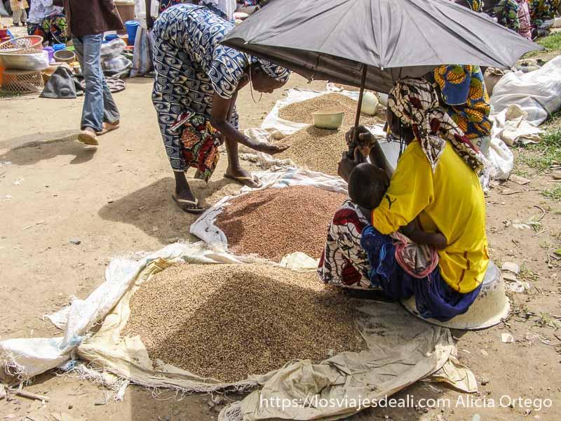 puesto de mijo con diferentes variedades y vendedora refugiándose del sol con paraguas