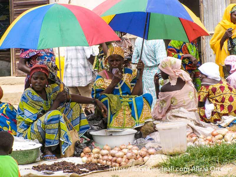vendedoras bajo paraguas de colores