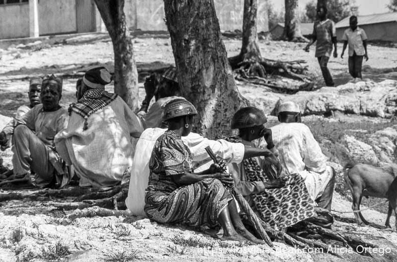 mujeres con sombrero calabaza sentadas junto a hombres a la sombra mercado de tourou