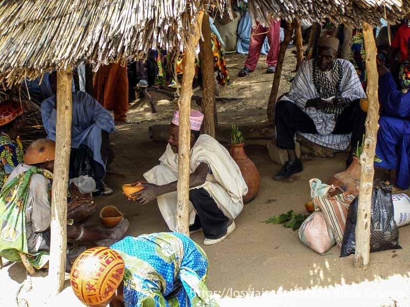 hombres bebiendo cerveza en pequeñas calabazas mercado de tourou