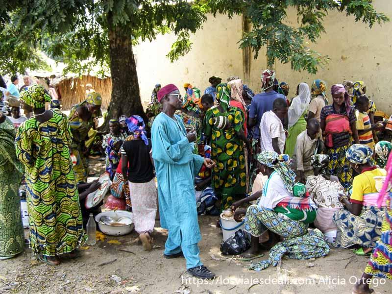 mujeres vestidas con telas de colores alrededor de puestos del mercado de tourou
