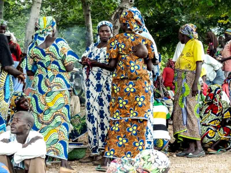 mujeres con vestidos de colores hablando y una con bebé a la espalda montes mandara