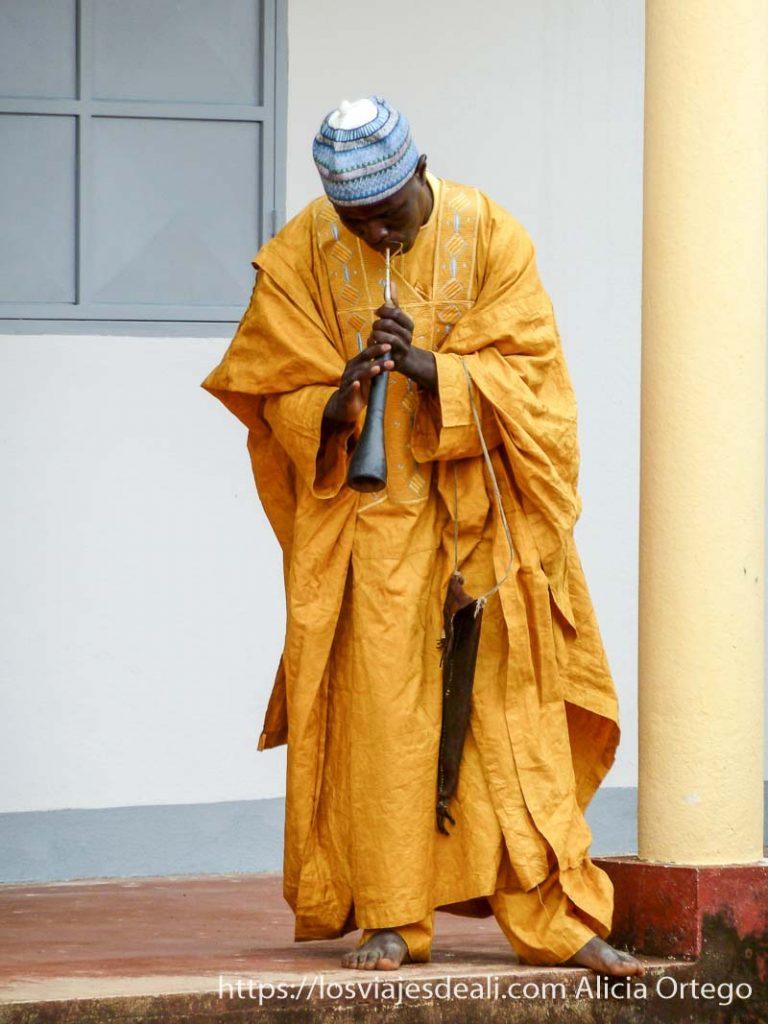 músico con vestido amarillo y bordados azules tocando una trompeta ngaoundere