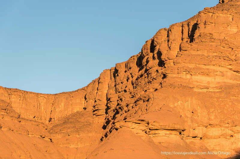 luz de amanecer iluminando montaña de roca paisajes del sahara