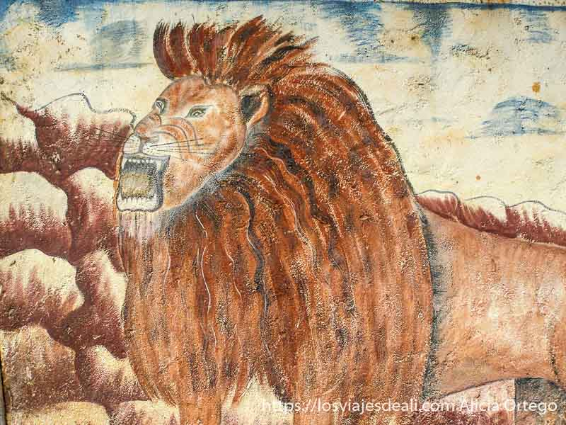 pintura de un león rugiendo en la puerta del palacio del reino de bafut