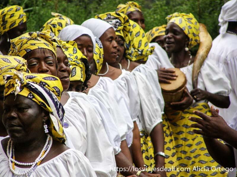mujeres con pañuelos amarillos en la cabeza y camisa blanca a punto de entrar en la iglesia reino de bafut