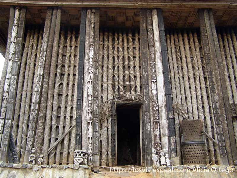 antiguo palacio de madera con columnas llenas de grabados en el reino de bafut