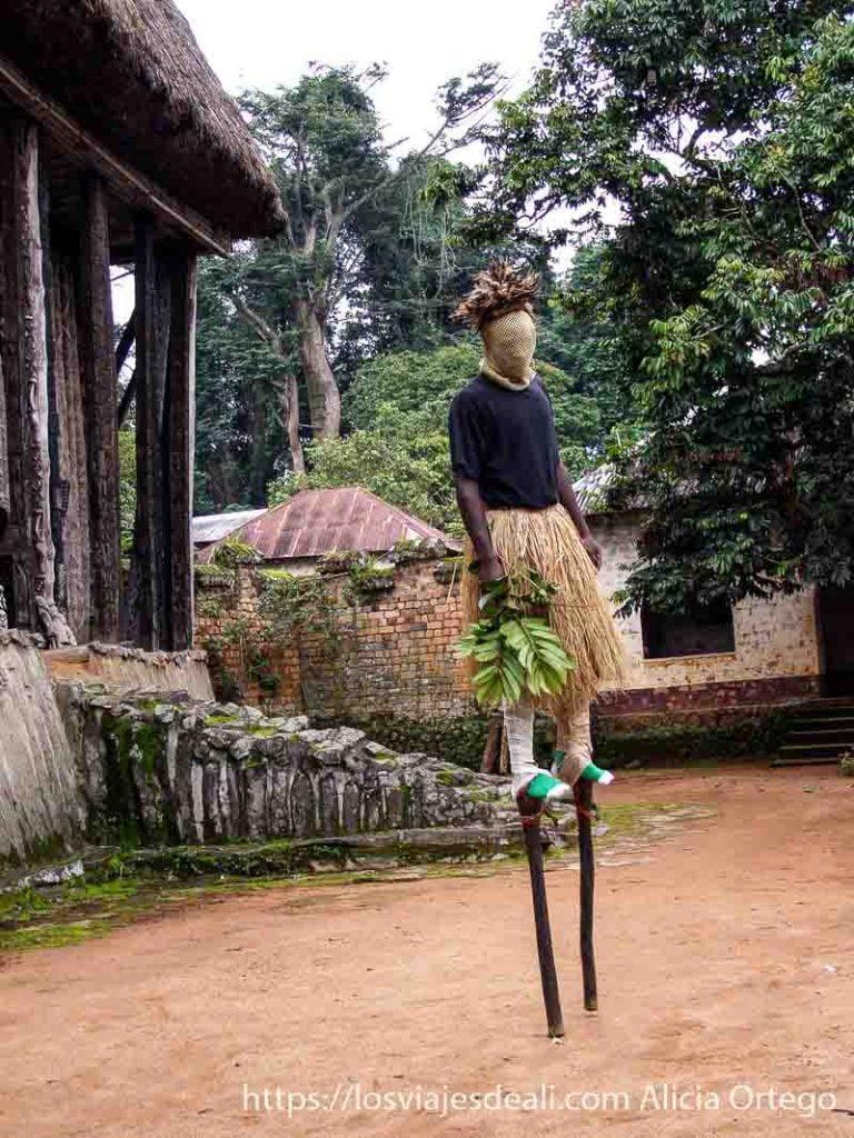 danzarín del reino de bafut sobre palos con cara tapada por malla