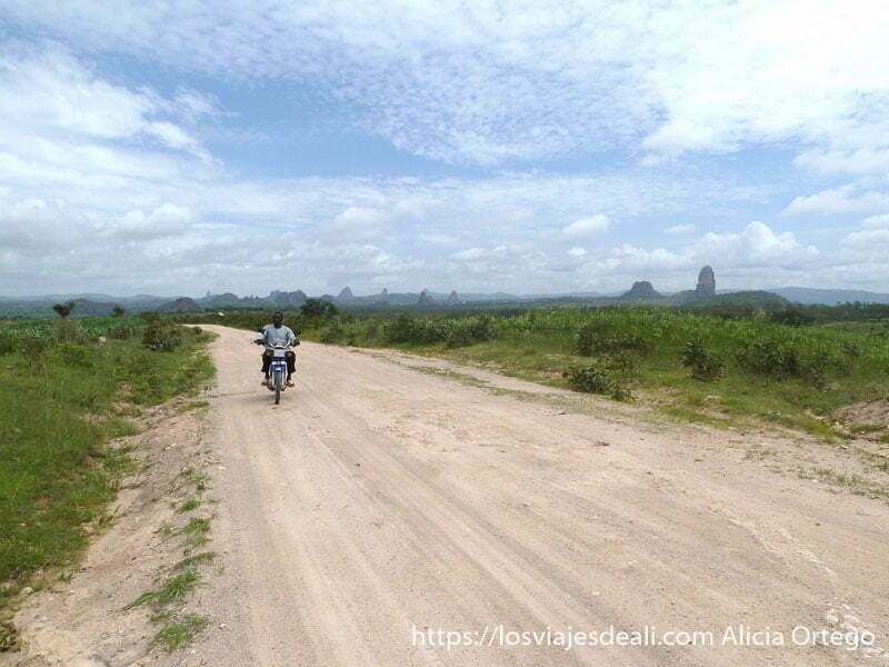 carretera con paisaje de agujas de roca al fondo y motorista rumsiki camerún