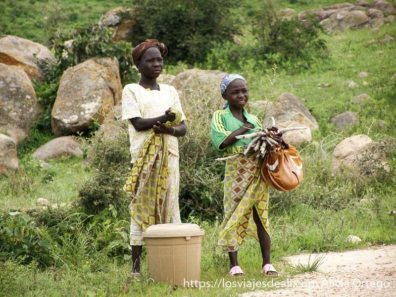 niñas con bolsas y leña en la carretera a rumsiki camerún