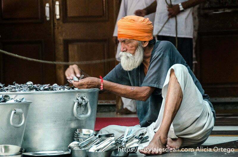 hombre mayor revisando cucharas ene l templo dorado de los sijs