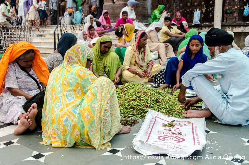 mujeres y un hombre limpiando guindillas en el templo dorado de los sijs